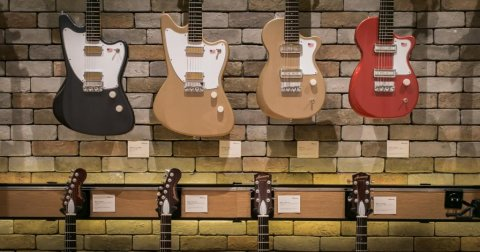 Harmony Electric Guitars hanging from a brick wall in a music store