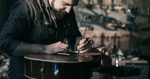 Guitar technician servicing an acoustic guitar