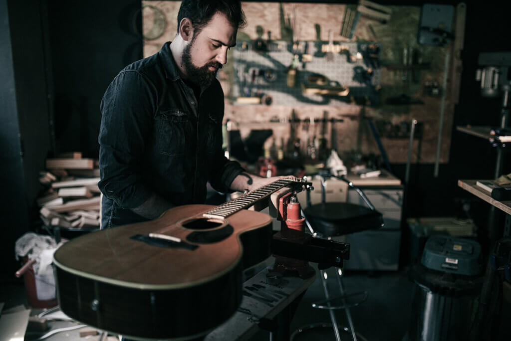 James of Well Played Gear inspecting an acoustic guitar
