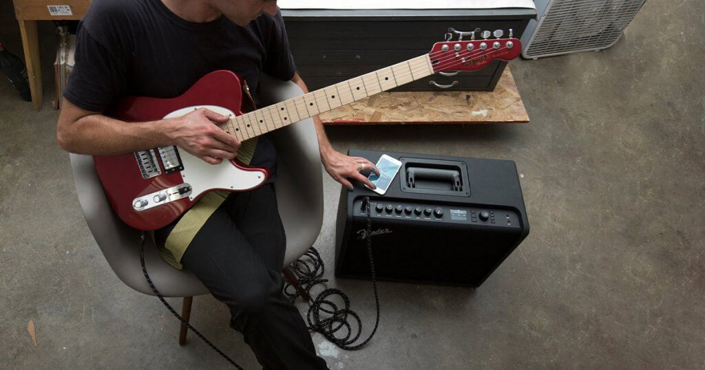 A man with an electric guitar, using a smart phone with his practice guitar amp